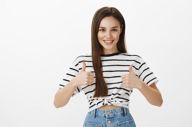 Chica atractiva segura que muestra el pulgar hacia arriba, gesto bien hecho, felicita la buena elección