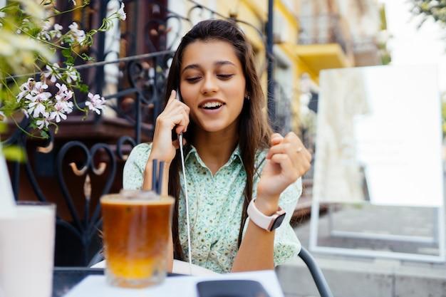 Chica atractiva sentada al aire libre en la terraza del café de la calle, hablando por teléfono inteligente, amigo de llamada