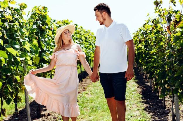 Chica atractiva con un sombrero de paja y un vestido beige camina con hermosa morena en el viñedo