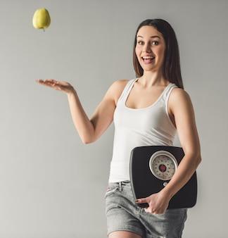 Chica atractiva sostiene balanzas, arrojando una manzana
