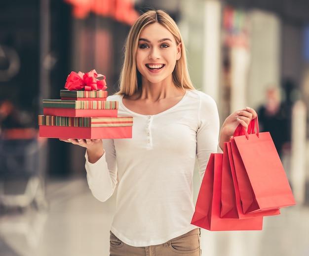 Chica atractiva sostiene bolsas de compras y cajas de regalo