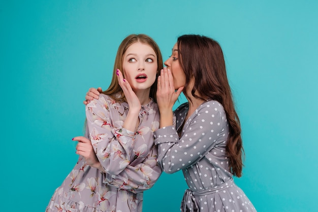 Chica atractiva susurra un secreto a su novia aislada sobre fondo azul
