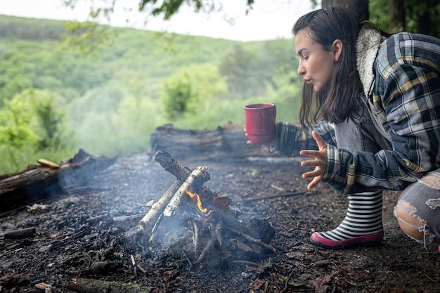Una chica atractiva con una taza en la mano se calienta cerca de un fuego en el bosque.