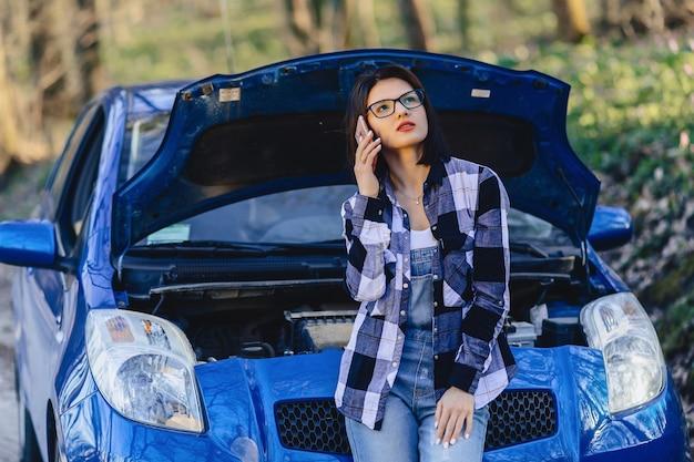 Chica atractiva con teléfono cerca de capó abierto de coche