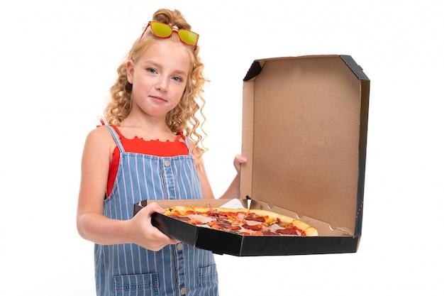 Chica atractiva tiene una caja abierta con pizza en un blanco