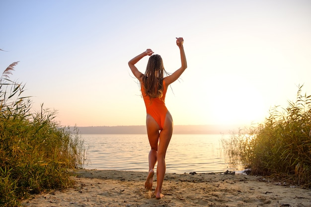 Chica atractiva en traje de baño en la playa al amanecer.