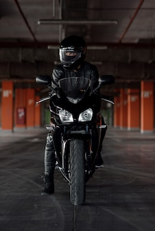 Chica atractiva en uniforme protector negro, guantes y casco integral montando en su motocicleta en un estacionamiento subterráneo.