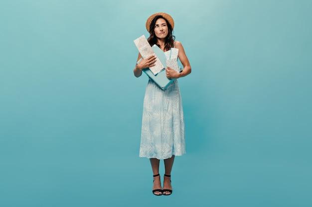 Chica atractiva en vestido midi posando pensativamente sobre fondo azul y sosteniendo la maleta, guía y boletos