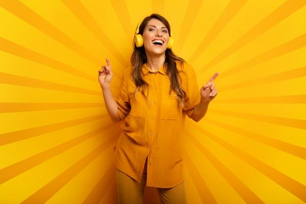 Chica con auriculares amarillos escucha música y bailes. expresión emocional y energética