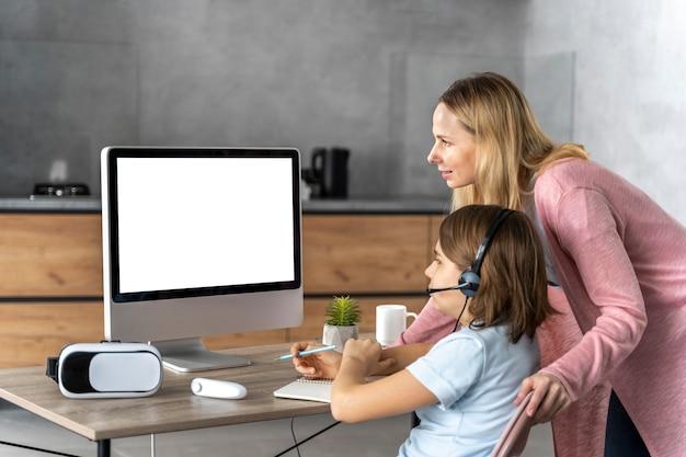 Chica con auriculares aprendiendo online con la madre a su lado