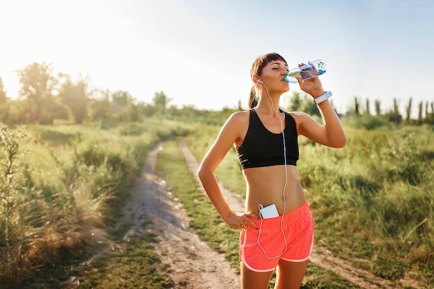 Chica en auriculares bebiendo agua después de correr