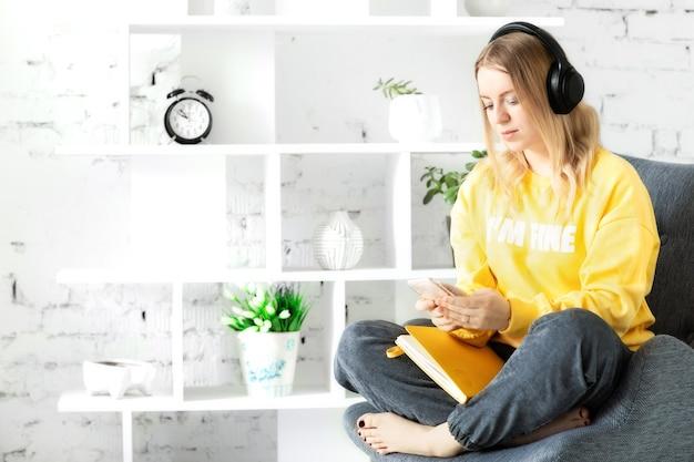 Chica en auriculares en blusa amarilla sentarse, relajarse en el sofá gris, usar el teléfono inteligente y la nota para escuchar música