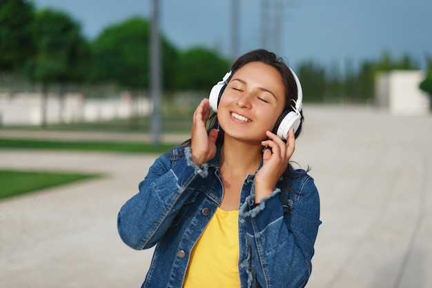 Chica con auriculares caminando en el parque en un día soleado y escuchando música