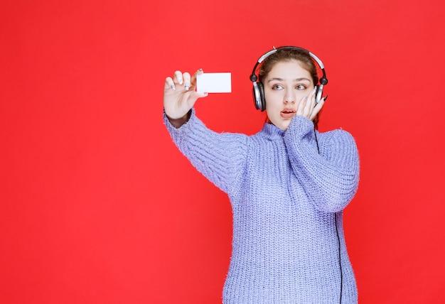 Chica con auriculares sosteniendo una tarjeta de visita y parece sorprendida.