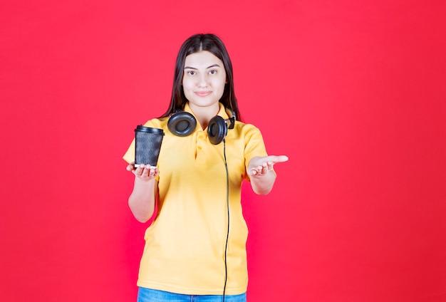 Chica con auriculares sosteniendo una taza de bebida desechable negra y llamando a la persona que está adelante