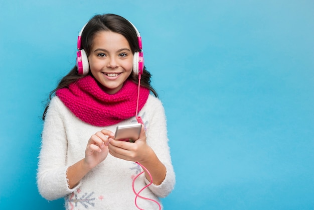Chica con auriculares y teléfono inteligente sobre fondo azul