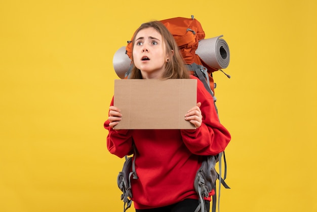 Chica autoestopista vista frontal con mochila sosteniendo cartón en blanco mirando hacia arriba