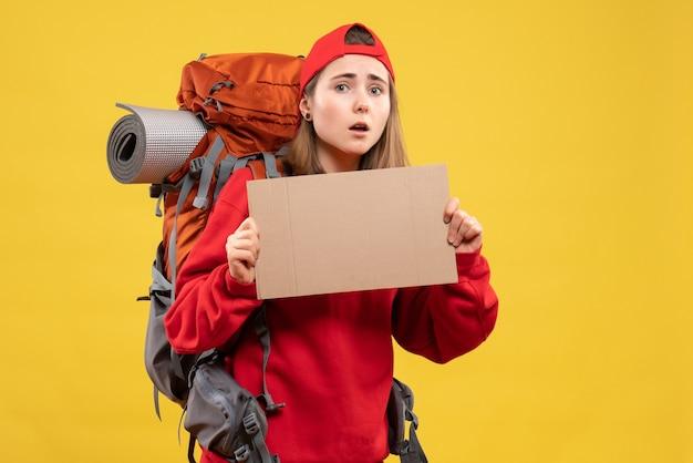 Chica autoestopista vista frontal con mochila sosteniendo cartón en blanco