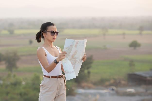 Chica aventurera navegando con un mapa topográfico en las hermosas montañas.