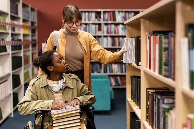Chica ayudando a su colega en silla de ruedas a elegir un libro para un proyecto