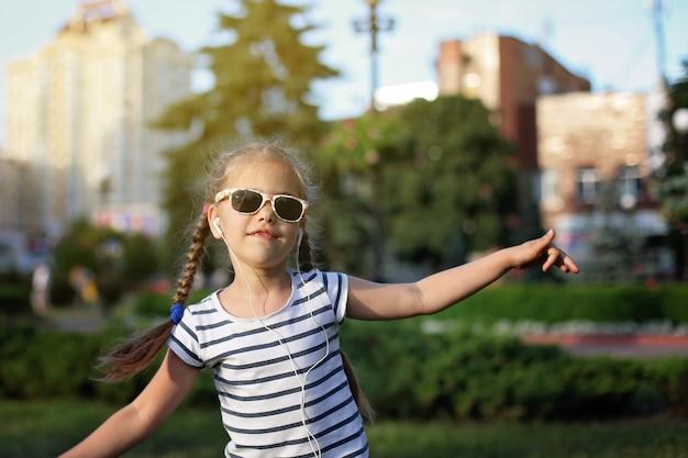 Chica bailando con auriculares en la calle