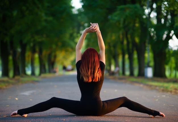 Chica bailando en un cuerpo negro en el jardín de verano.