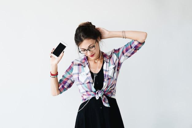 Chica bailando y mostrando el teléfono