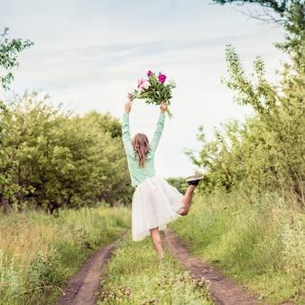 Chica bailando en la naturaleza con un ramo de flores