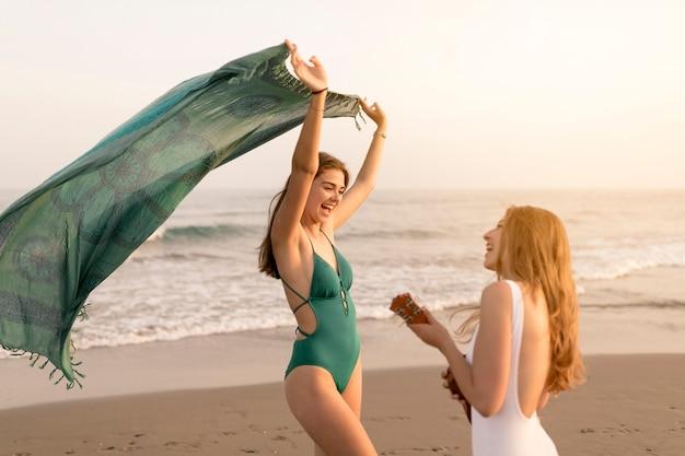 Chica bailando con su amiga jugando ukelele en la playa de arena