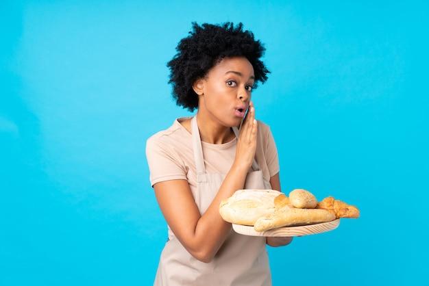 Chica baker cogiendo panes sobre fondo azul.