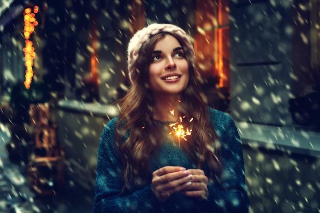 Chica con una bandera de invierno de luces de bengala