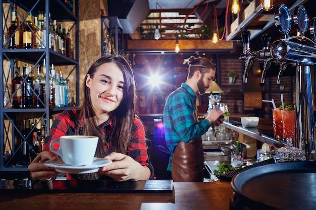 Chica barman barista sostiene una taza de café en un bar.