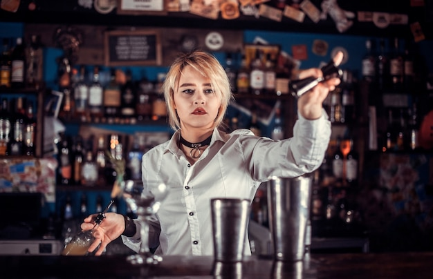Chica barman crea un cóctel en la porterhouse