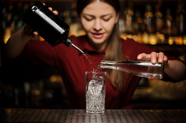 Chica de barman prepara un cóctel alcohólico caipirinha, vertiendo de dos botellas
