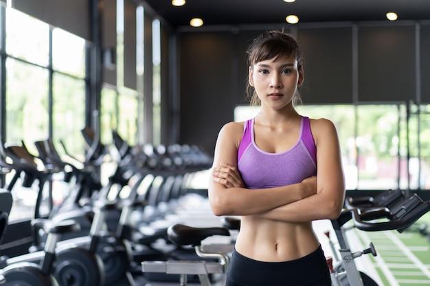 Chica bastante asiática con seis paquetes de ropa deportiva de color púrpura de pie y cruzando los brazos en el gimnasio o gimnasio.