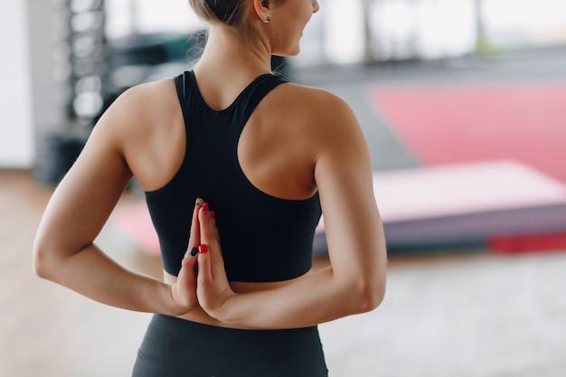 Chica bastante atractiva haciendo yoga en una habitación luminosa