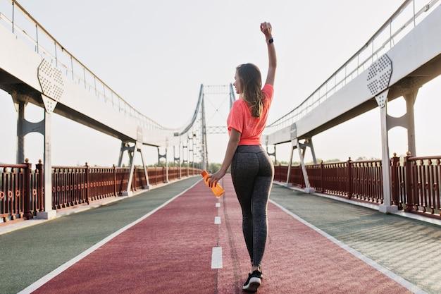Chica bastante blanca que se extiende en el estadio temprano en la mañana. foto al aire libre de la parte posterior de la refinada mujer haciendo fitness.