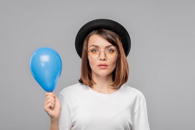 Chica bastante seria con sombrero y camiseta sosteniendo un globo azul mientras te felicita por el feliz cumpleaños