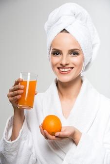 Chica en bata de baño beber jugo de naranja.