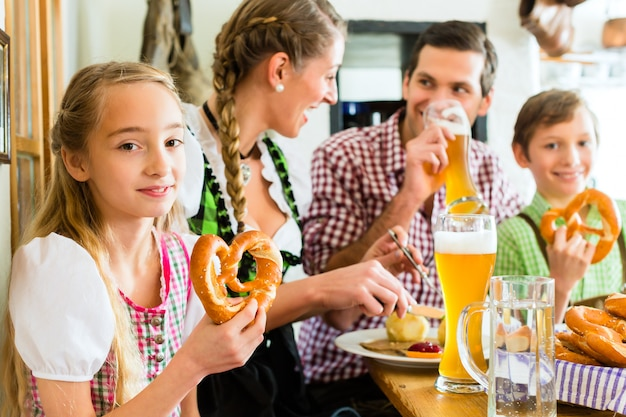 Chica bávara con familia en restaurante.