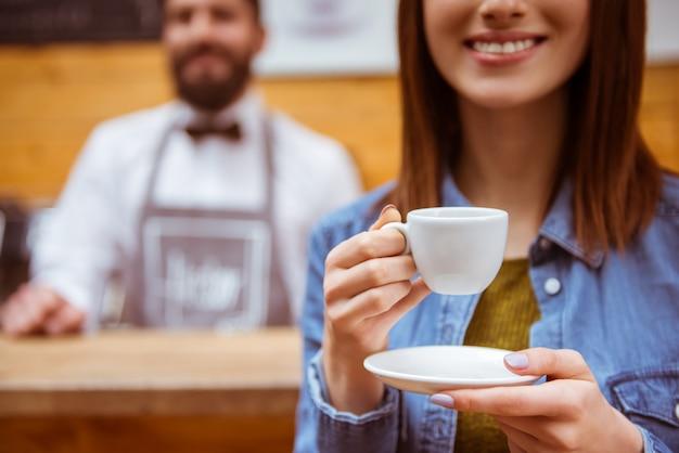 Chica bebe café en una cafetería y sonríe.