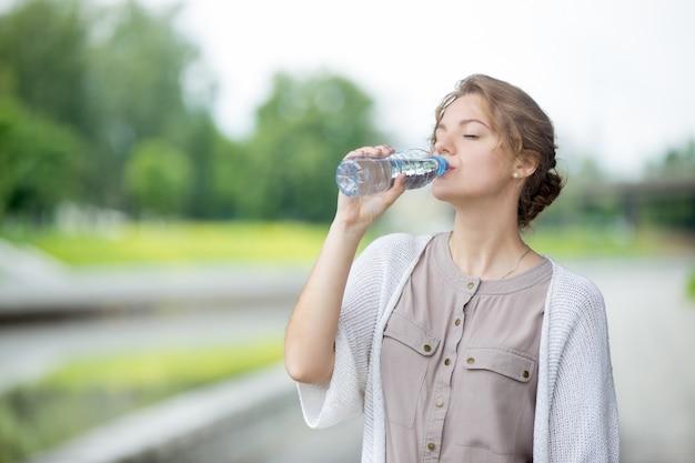 Chica bebiendo agua con el fondo borroso