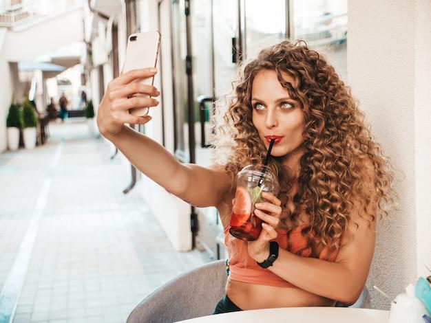Chica bebiendo batido fresco en vaso de plástico con paja y tomando una selfie
