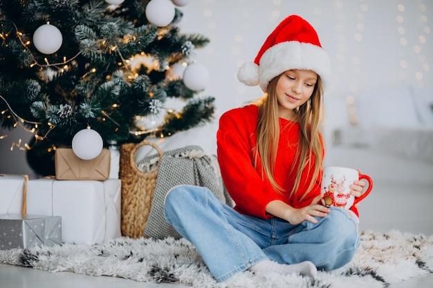 Chica bebiendo cacao por árbol de navidad