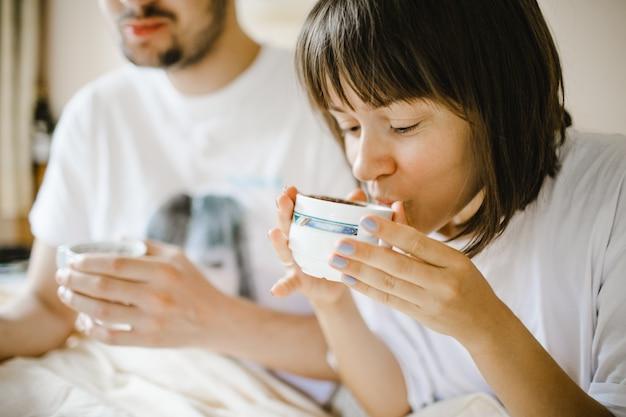 Chica bebiendo café caliente en la mañana con novio