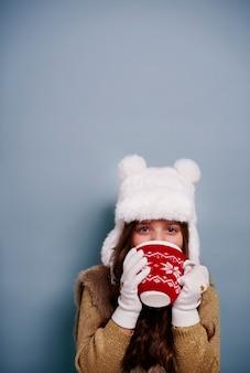 Chica bebiendo chocolate caliente en tiro de estudio
