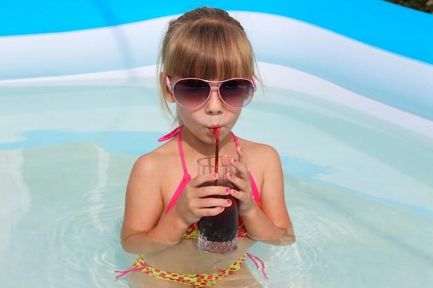 Chica bebiendo jugo en la piscina.