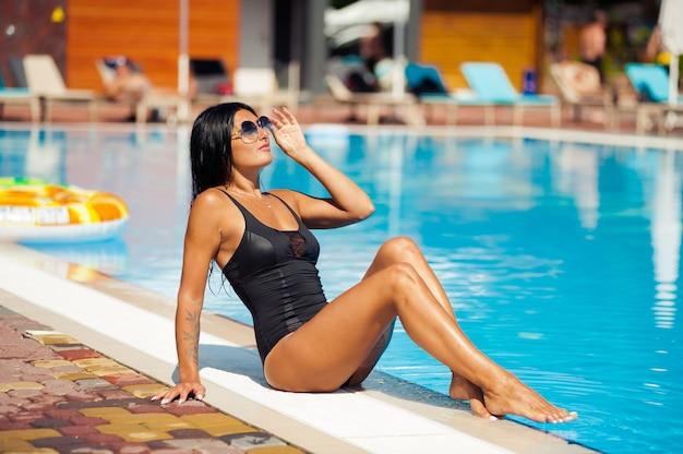 Chica bella y sexy en traje de baño relajante junto a la piscina