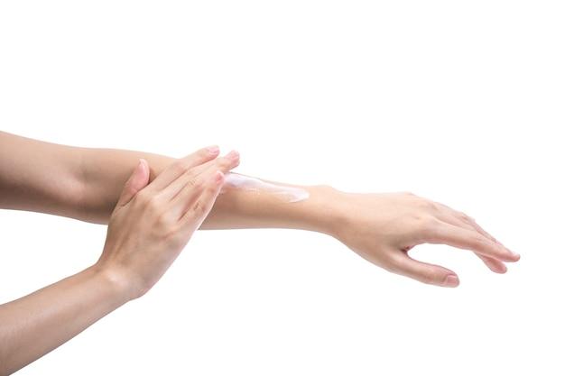 Chica de belleza aplicando algo de loción blanca en su mano