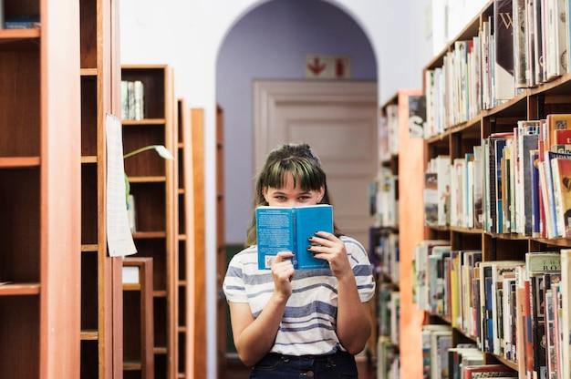 Chica en biblioteca escondiendo su cara detrás de un libro